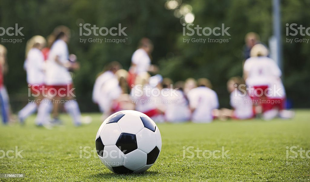 Close-up of a Soccer Ball in front of a Female Soccer Team stock photo