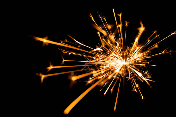 close-up of a sparkler on black background - sparkler stock pictures, royalty-free photos & images