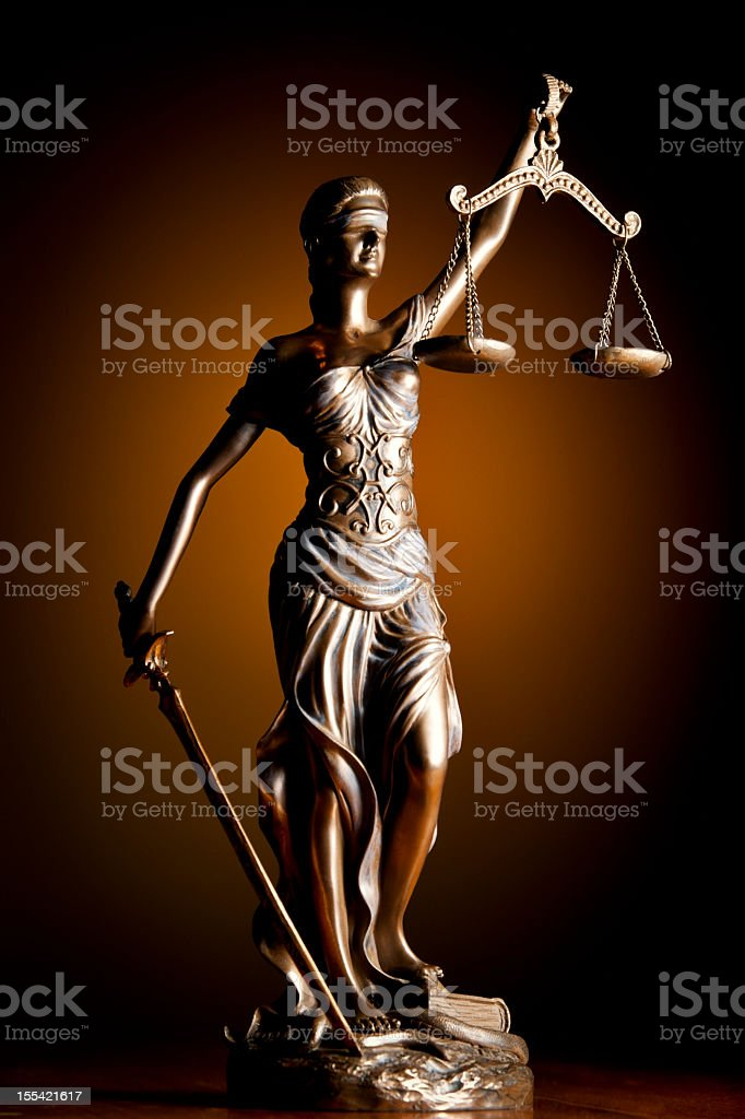 Close-up of a statue of Themis over a brown background stock photo