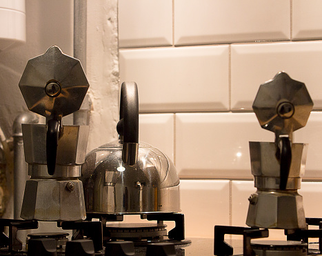 Close-up of a steel kettle and two aluminum moka pots standing on a gas stove of a house with white metro-retro ceramic wall decoration in the background