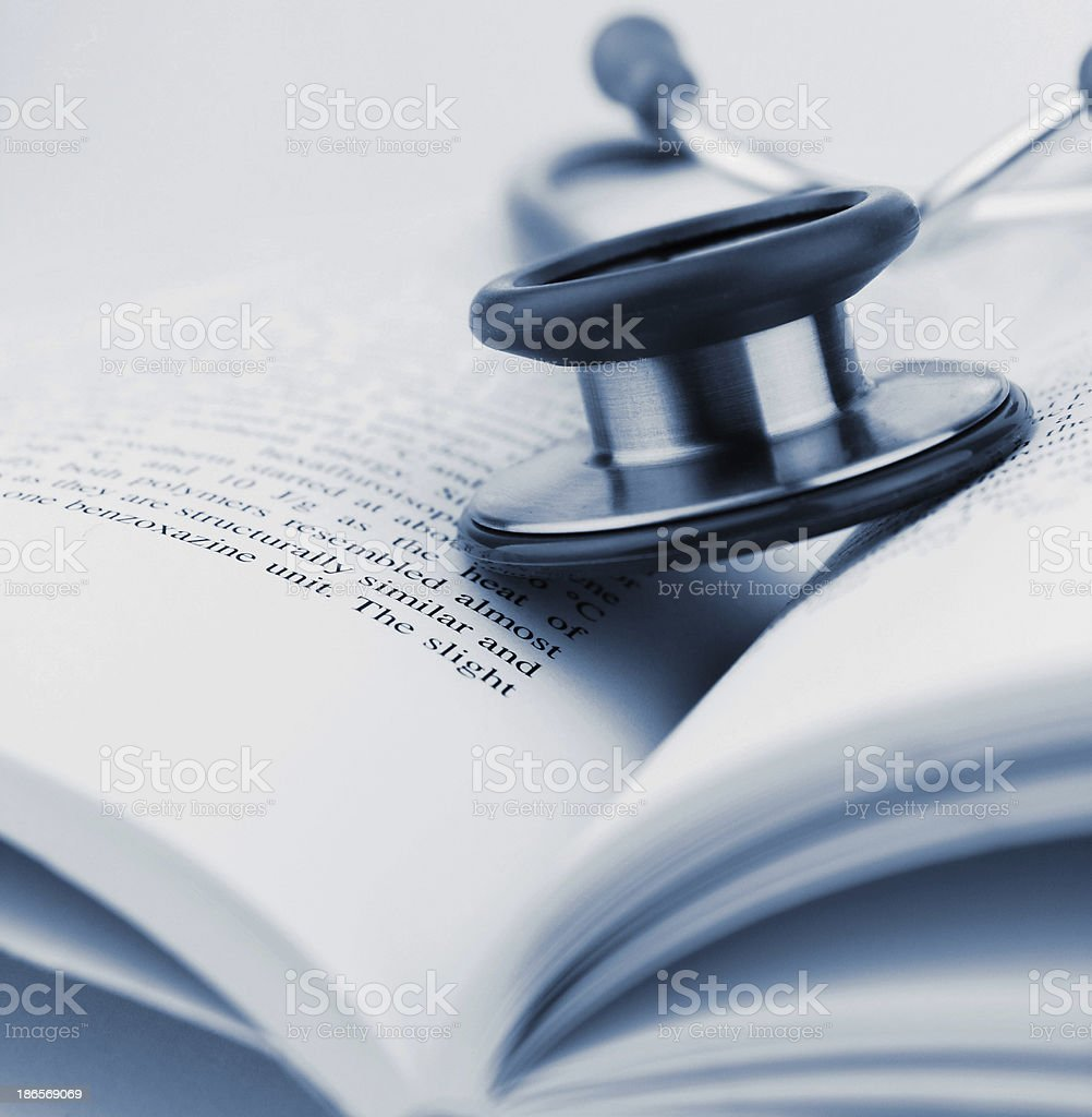 A close-up of a stethoscope resting on an open book royalty-free stock photo