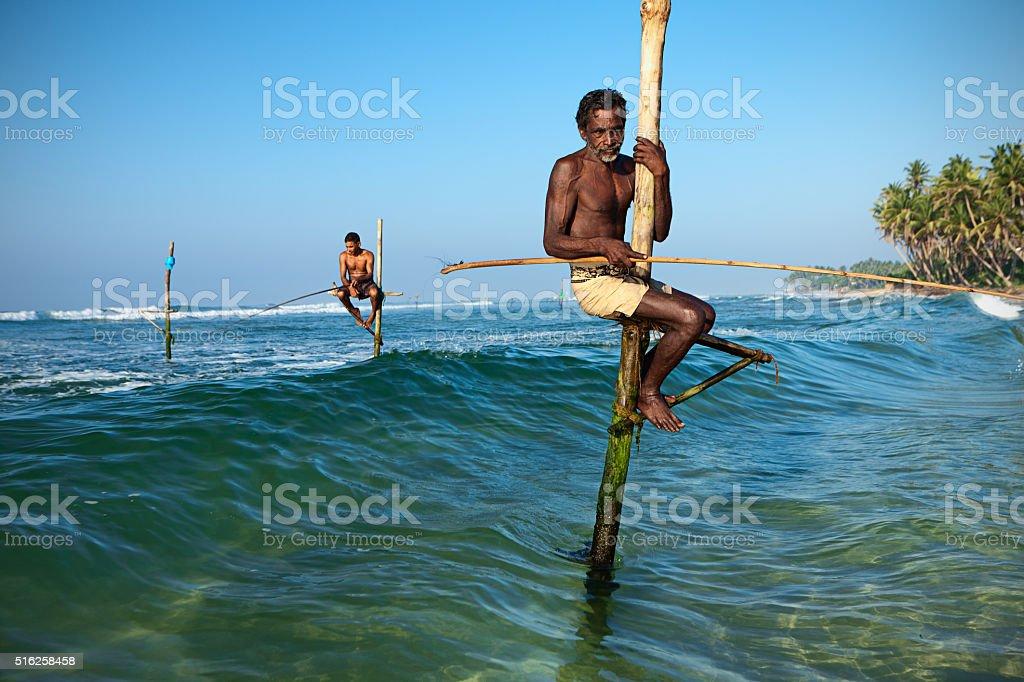 Close-up of a stilt fishermen in action, Ceylon stock photo