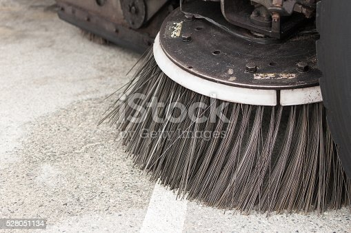 A close-up of a street sweepers brush. The cleaning equipment is mounted to a truck that is driven through the streets to sweep and vaccum up trash in the streets.