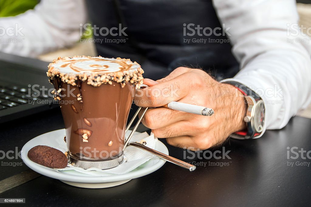 closeup of a Stylish man with laptop, coffee and cigarette. stock photo