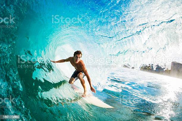 Photo of Close-up of a surfer riding a large blue wave