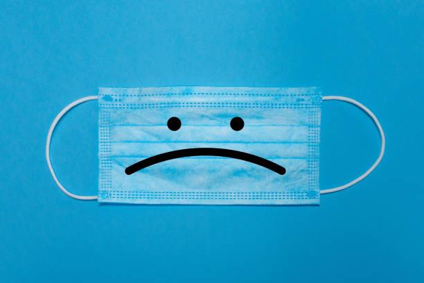 primo piano di una maschera chirurgica su sfondo blu con un viso triste. concetto di tristezza causato da covid-19, nuovo normale e blue monday. - blue monday foto e immagini stock