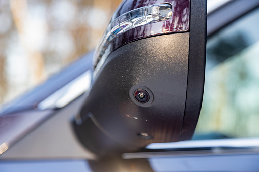 closeup of a surround view camera in the side mirror of a modern car rear view. camera of parking assuist