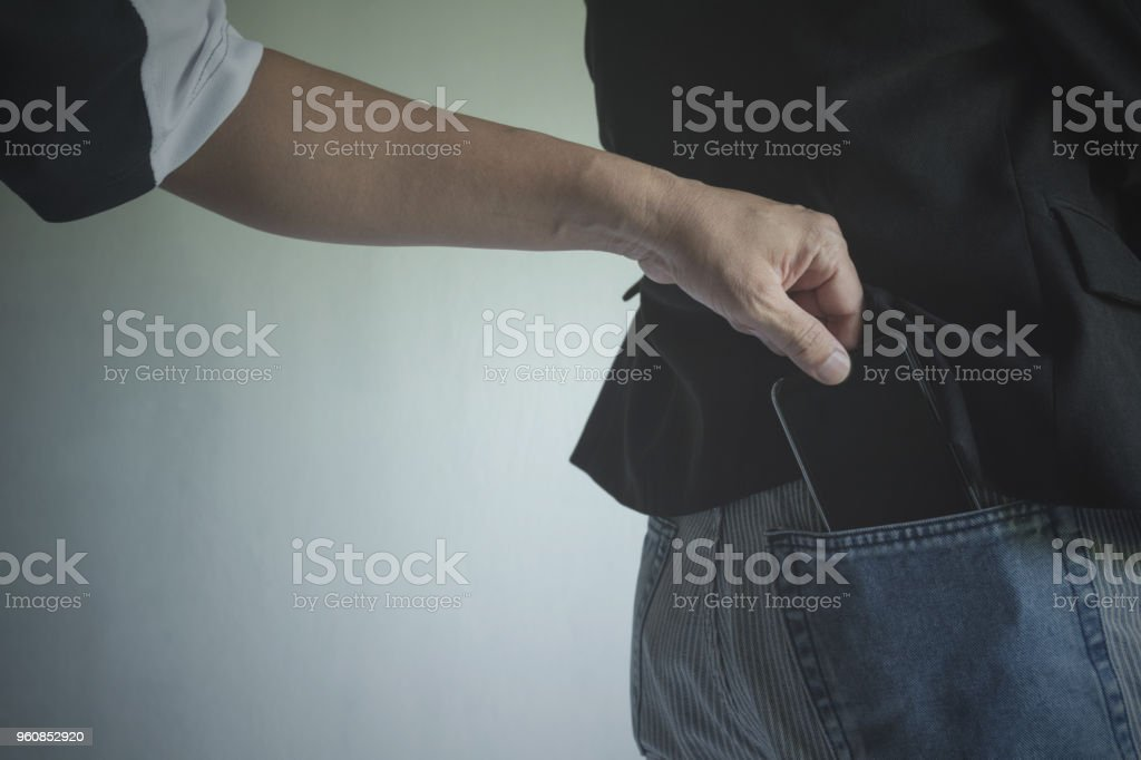 Close-up of a the hand of thief stealing the wallet to a woman. Thief stealing wallet from back pocket of a woman. stock photo