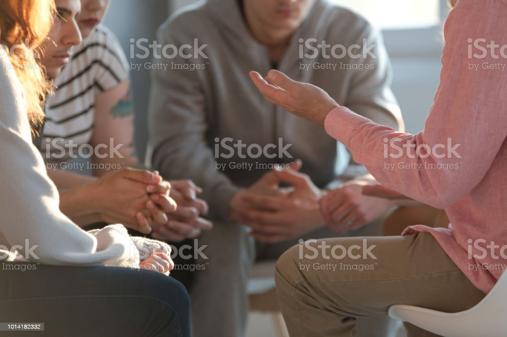 Close-up of a therapist gesticulating while talking to a group of listing teenagers during an educational self-acceptance and motivation meeting. stock photo
