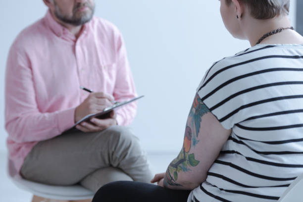 Close-up of a therapy specialist taking notes while listening to a tattooed young person with emotional and behavioral problems in a juvenile detention center. stock photo