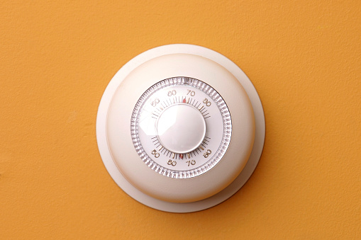 A Closeup Of A Thermostat On A Orange Wall Set To 68 Degrees Stock Photo - Download Image Now