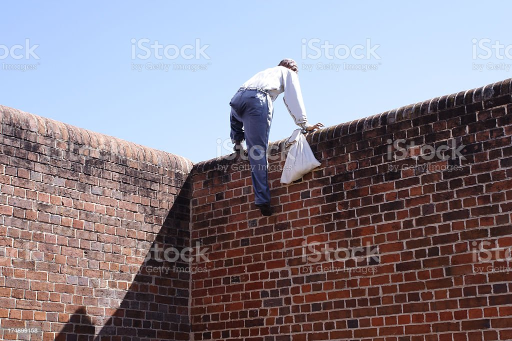 Close-up of a thief climbing over a brick wall stock photo
