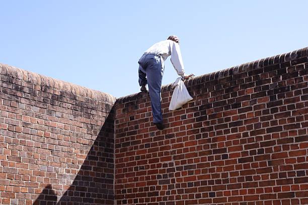 Close-up of a thief climbing over a brick wall stock photo