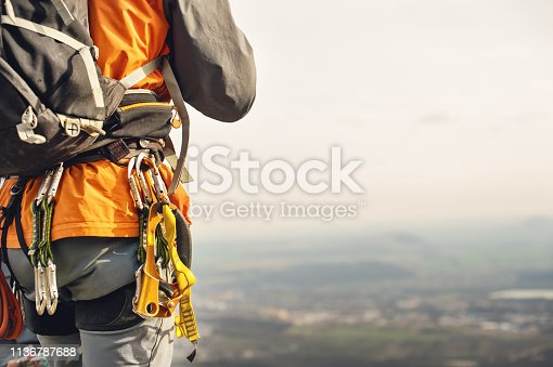 istock Close-up of a thigh climber with equipment on a belt, stands on a rock 1136787688
