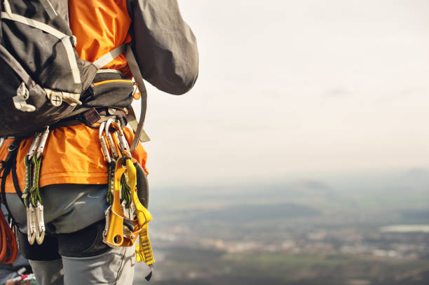 Close-up of a thigh climber with equipment on a belt, stands on a rock stock photo