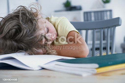 1020504438istockphoto Close-up of a tired kid sleeping with his head rested on a table with a book. 1064904456