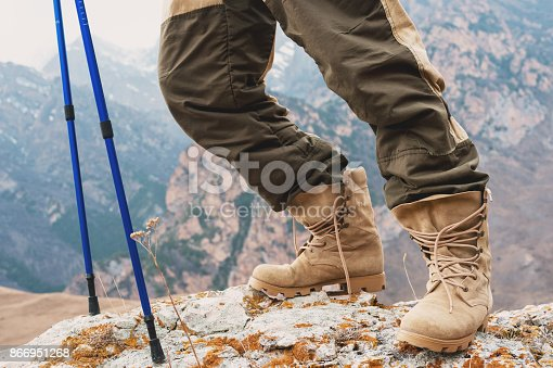 istock Close-up of a tourist's foot in trekking boots with sticks for Nordic walking standing on a rock stone in the mountains 866951268