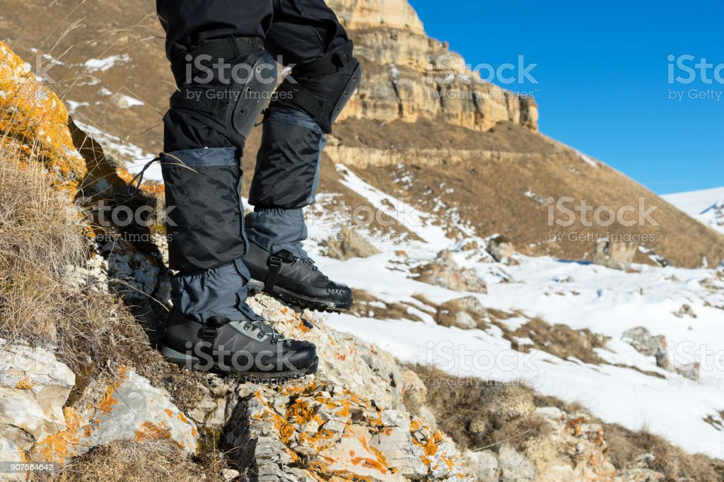 Closeup Of A Tourists Foot In Trekking Boots With Sticks For