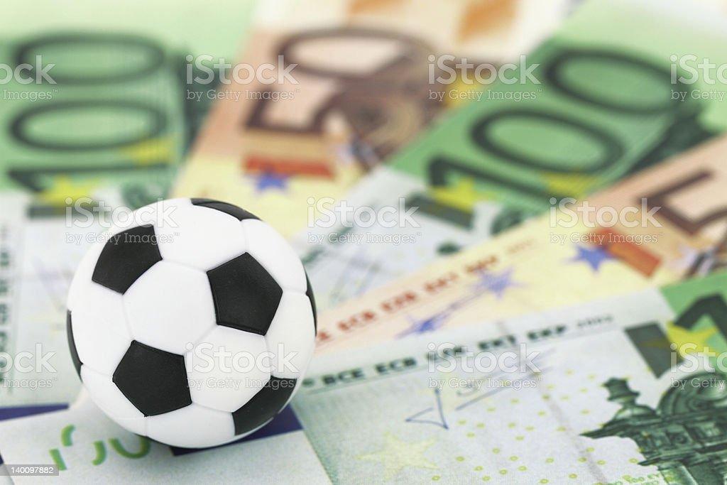 Close-up of a toy soccer ball atop European money bills stock photo