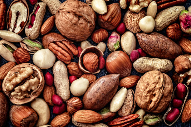 close-up of a variety of dried fruit and nuts on a table - frutos secos imagens e fotografias de stock