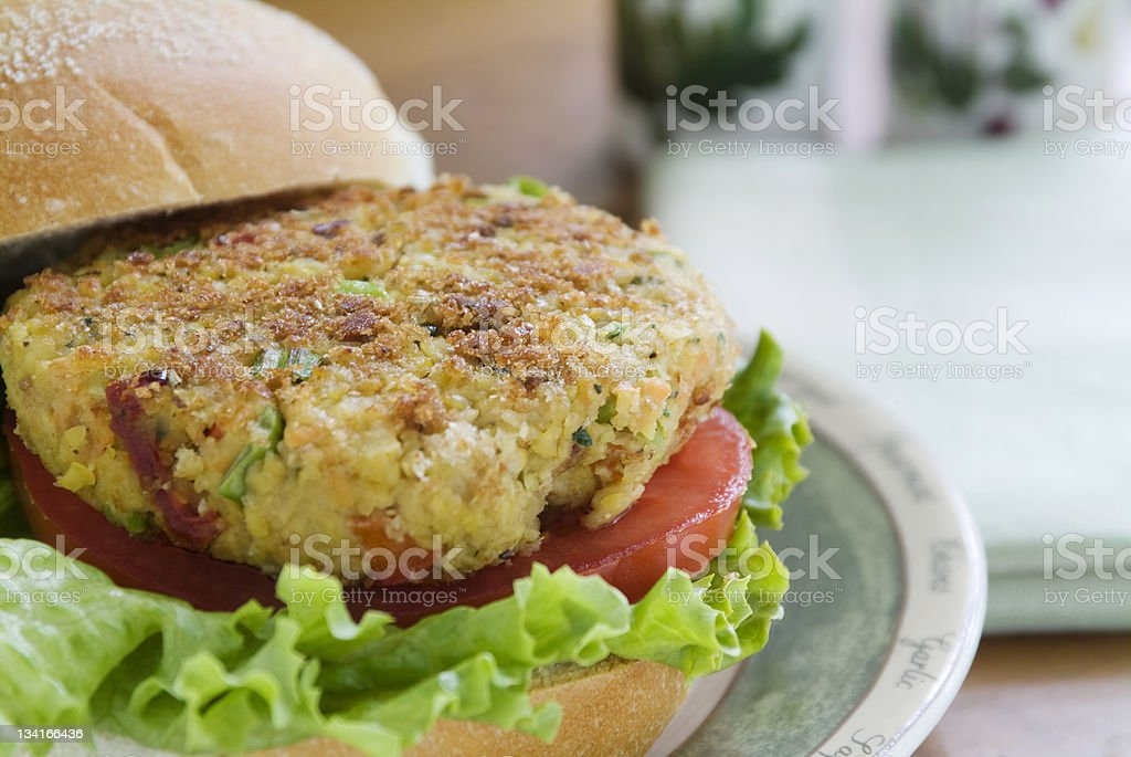 Close-up of a veggie burger with lettuce and tomatoes stock photo