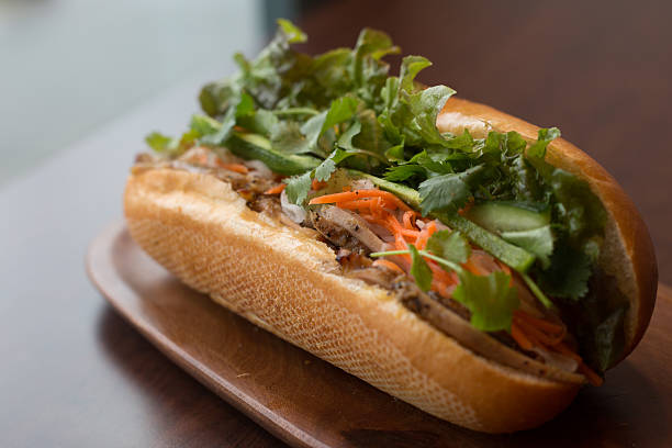 Closeup of a Vietnamese Banh mi sub sandwich A healthy sub sandwich / Vietnamese banh mi filled with meat and healthy veggies by a window. bánh mì sandwich stock pictures, royalty-free photos & images