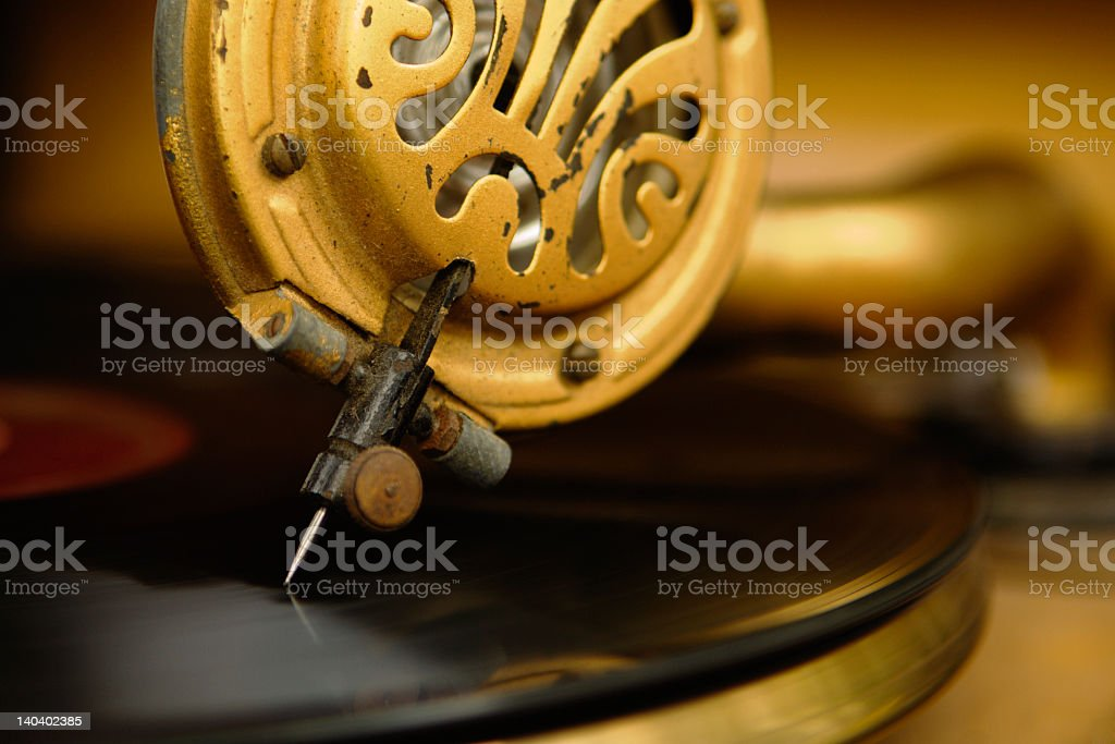 A closeup of a vintage record player needle playing a record stock photo