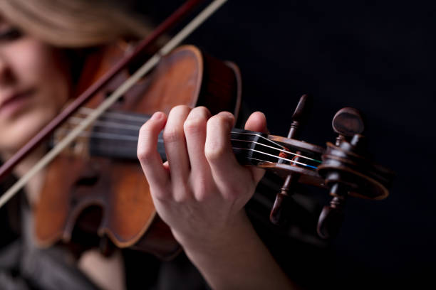 closeup of a violinist's hand playing Young beautiful woman violinist player playing her instrument on her shoulder holding bow. portrait in a blurred dark room in background. Concept of classical music folk music stock pictures, royalty-free photos & images