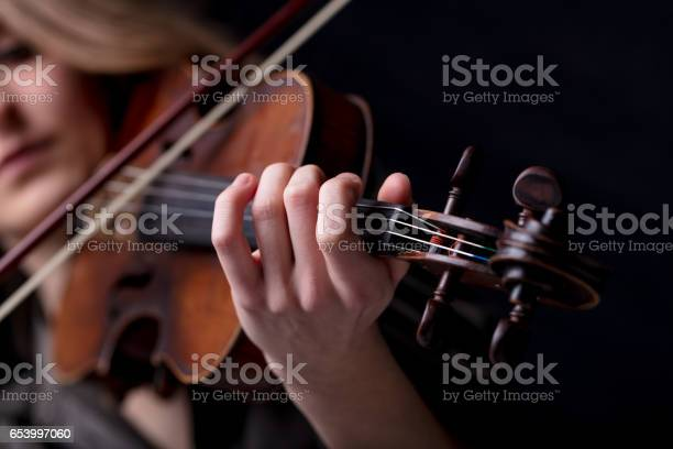 Young beautiful woman violinist player playing her instrument on her shoulder holding bow. portrait in a blurred dark room in background. Concept of classical music