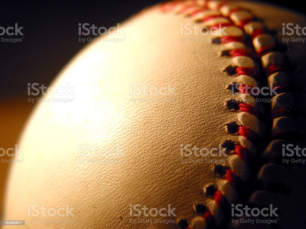 Close-up of a white baseball with red stitches stock photo