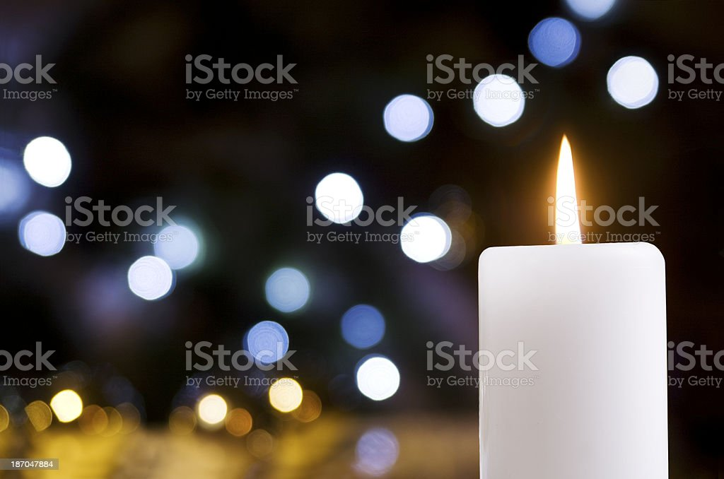 Close-up of a white candle with glittering lights stock photo