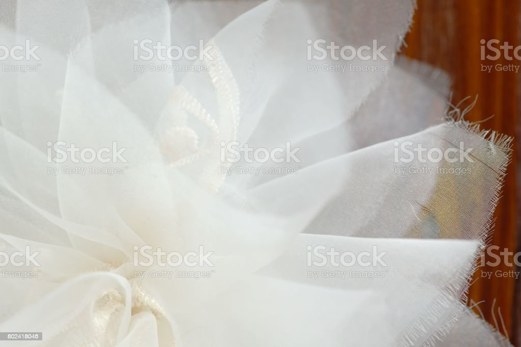 Closeup of a white chiffon bow over a brown wooden surface stock photo
