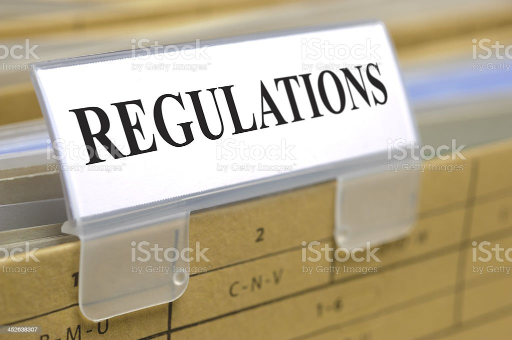 Close-up of a white clipped tag that says REGULATIONS royalty-free stock photo
