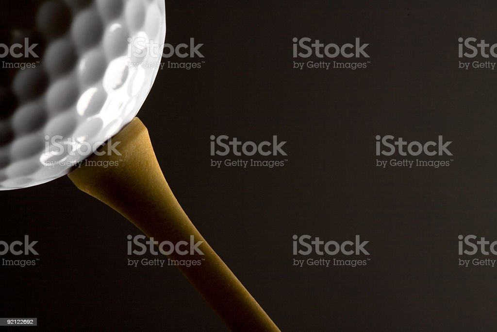 Closeup of a white golf ball on a wooden tee royalty-free stock photo