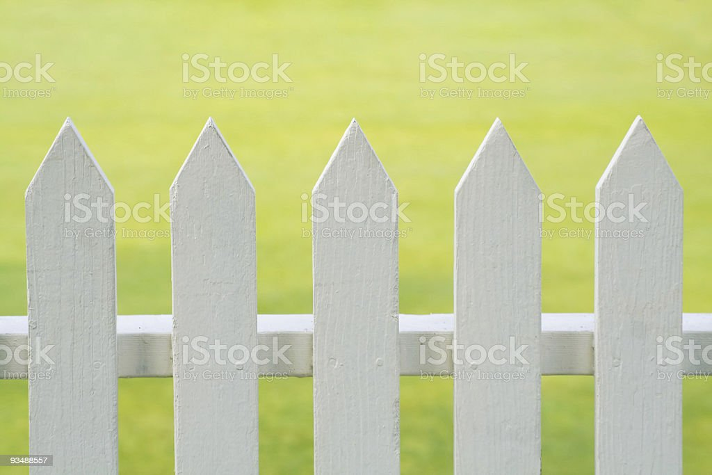 Close-up of a white picket fence near grass royalty-free stock photo