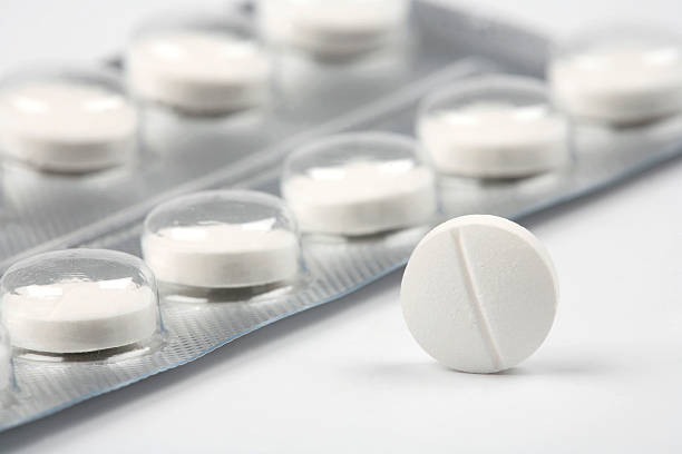 a close-up of a white pill with the package behind it - ağrı kesici stok fotoğraflar ve resimler