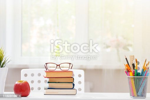 istock Close-up of a white schoolchild desktop. On the table is a stack of books. Light from the window. Blurred background. 1150916614