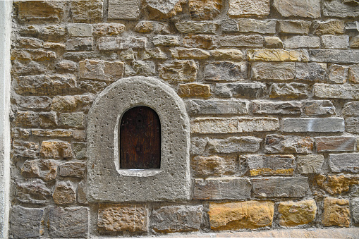 Close-up of a wine window (buchetta del vino), used in the past to sell wine directly to passers-by, on the old stone wall of an ancient building in the historic centre of Florence, Tuscany, Italy