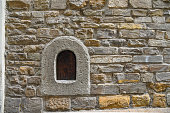 Detail of an old stone wall with a wine window (buchetta del vino) in a street of the historic centre of Florence, Tuscany, Italy