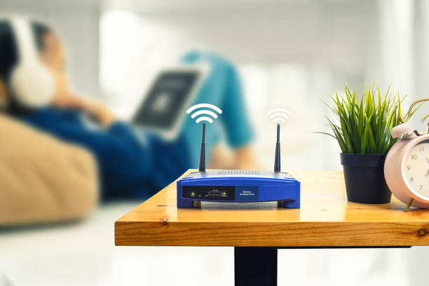closeup of a wireless router and a man using smartphone on living room at home ofiice - router foto e immagini stock
