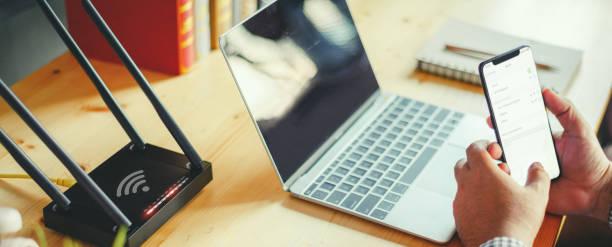 Nahaufnahme eines drahtlosen Routers und eines Mannes mit Smartphone auf Wohnzimmer zu Hause Ofiice, Concepts Wi-Fi verbinden. – Foto