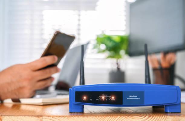 Nahaufnahme eines WLAN-Routers und eines Mannes mit Smartphone im Wohnzimmer von iice – Foto
