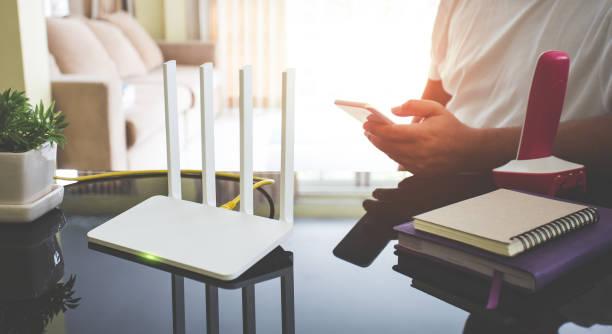 Nahaufnahme von einem wireless-Router und ein junger Mann mit Smartphone im Wohnzimmer zu Hause – Foto