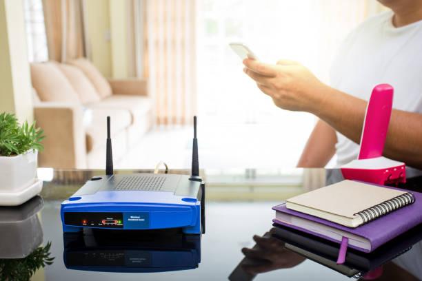nahaufnahme eines drahtlosen routers und eines jungen mannes mit smartphone im wohnzimmer zu hause - router stock-fotos und bilder