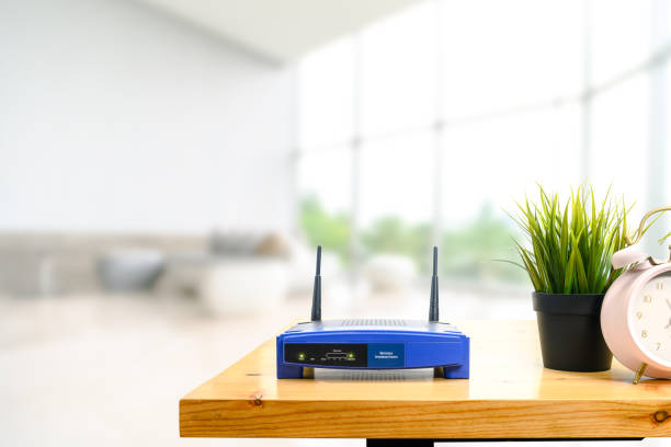 Nahaufnahme eines drahtlosen Routers auf dem Wohnzimmer zu Hause mit einem Fenster im Hintergrund – Foto