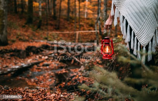 Rearview of a woman in a white poncho holding an old red lantern while walking through the forest.