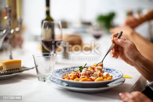 Close-up of a woman having pasta. Hand of a female eating pasta sitting at dining table.