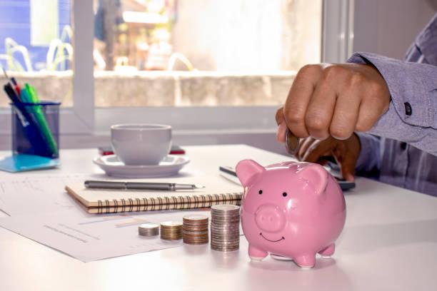 primer plano de una mujer sosteniendo una moneda en una alcancía y registrando ingresos, gastos, ideas para calcular gastos y ahorrar dinero. - gerente de cuentas fotografías e imágenes de stock