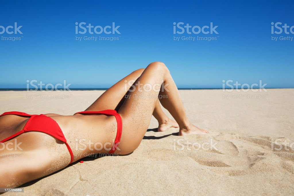 A closeup of a woman in a bikini, lying on a sandy beach stock photo