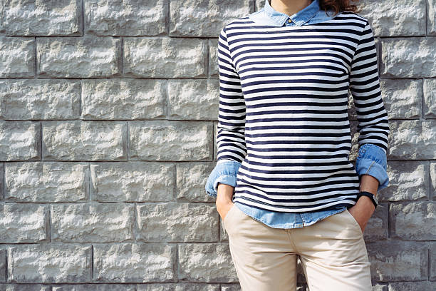 close-up of a woman in a denim shirt, striped t-shirt - moda preppy fotografías e imágenes de stock
